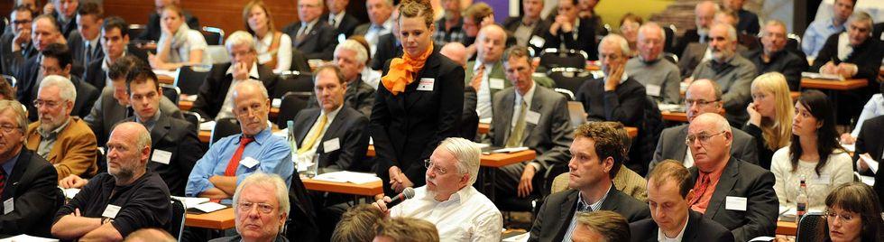 Zuschauermenge einer Fachkonferenz. Eine Frau reicht einem Fragesteller ein Mikrophon.