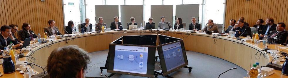Eine große Besprechungsrunde aus einem Beteiligungsverfahren in NRW. Im Zentrum stehen Computermonitore.